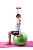 Pretty brunette exercising with dumbbells on fitness ball Royalty Free Stock Photos