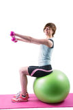 Pretty brunette exercising with dumbbells on fitness ball Royalty Free Stock Photography