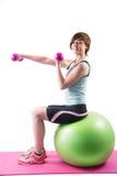 Pretty brunette exercising with dumbbells on fitness ball Stock Image