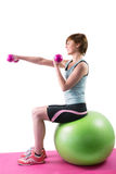 Pretty brunette exercising with dumbbells on fitness ball Stock Photography