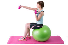 Pretty brunette exercising with dumbbells on fitness ball Stock Photos