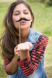 Pretty brunette with fake mustache Stock Photography