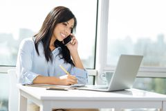 Pretty brunette female having friendly talk. Make notes. Charming office worker keeping smile on her face and using pencil while looking at screen of her Royalty Free Stock Image