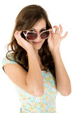 Pretty brunette female peering over her sunglasses Stock Photos