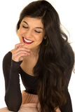 Pretty brunette female sitting smiling hand on chin looking down Royalty Free Stock Photography