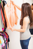Pretty brunette in front of a closet Stock Images