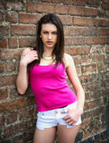 Pretty brunette girl against brick wall, casual clothes Royalty Free Stock Images