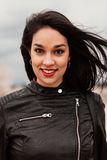Pretty brunette girl with black leather jacket Stock Images