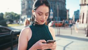 Pretty brunette girl dreamily looking on her cellphone screen, charmingly smiling and texting message while standing in. The city center. City settings stock footage