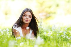 Pretty brunette girl laying on grass Royalty Free Stock Image