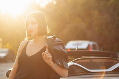 Pretty brunette girl in leather jacket posing near convertible car with a sun light. Space for text. Pretty brunette woman in leather jacket posing near royalty free stock images