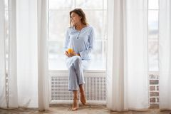 Pretty brunette girl in the light-blue pajama sits with a glass of fresh juice in her hand on the windowsill on a large royalty free stock image