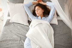 Pretty brunette girl in the light-blue pajama is sleeping on the bed under the beige blanket on the gray sheet royalty free stock images