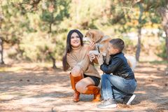 Pretty brunette girl and a little boy walking with dog in the park. Animal concept. Beautiful girl and a little boy having fun with doggie in the park outdoors Royalty Free Stock Image
