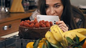 Pretty brunette girl making photos and videos of her freshly cooked raspberry cake. Amateur cooking, homemade pastry and stock footage