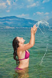 Pretty brunette girl, playing with water in the se Stock Photos