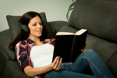 Pretty brunette girl reading and listening music on the sofa. Relax at home Stock Photo