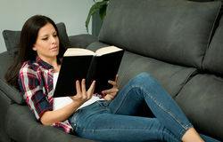 Pretty brunette girl reading on the sofa. Relax at home Royalty Free Stock Image