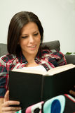 Pretty brunette girl reading on the sofa. Relax at home Stock Image