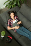 Pretty brunette girl reading on the sofa & x28;view from above& x29; Royalty Free Stock Photos