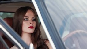 Beautiful fashion model is sitting in a passenger seat and waiting driver stock footage