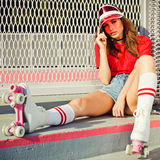 Pretty brunette girl in a red top and jeans shorts, red sunvisor and vintage roller derby has a rest sitting on the stairs Stock Photography