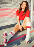 Pretty brunette girl in a red top and jeans shorts and vintage roller derby has a rest sitting on the stairs Stock Photos