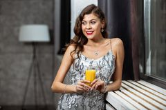 Pretty brunette girl in a shining gray evening dress holding a glass of juice is staying next to the windowsill royalty free stock image