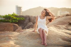 pretty brunette girl sits on stone Stock Photo