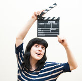 Pretty brunette girl smiling and showing clapper Royalty Free Stock Photo