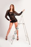 Pretty brunette girl standing at ladder Royalty Free Stock Photos