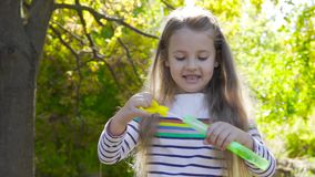 Pretty brunette girl staying in autumn sunrays and blowing soap bubbles. Little child in striped jacket playing in the. Park and smiling stock video