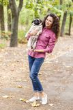 Pretty brunette girl walking with dog in the park. Animal concept. Beautiful girl with long hair having fun with doggie mops in the park outdoors. Young woman Royalty Free Stock Photos