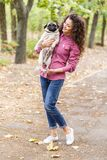 Pretty brunette girl walking with dog in the park. Animal concept. Beautiful girl with long hair having fun with doggie mops in the park outdoors. Young woman Stock Photography
