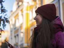 Pretty Brunette Girl Wearing Purple Winter Coat, Hat and Scarf, Walking by European Street at Winter, Using Her royalty free stock photo