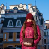Pretty Brunette Girl Wearing Purple Winter Coat, Hat and Scarf, Walking by European Street at Winter, Wrapped up in a Royalty Free Stock Photography
