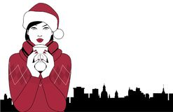 Pretty brunette girl wearing a santa claus hat drinking a hot drink at Christmas. City sky line in the background Royalty Free Stock Photo
