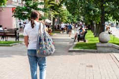 Pretty brunette girl or woman from behind in blue jeans, white shirt  and grey knitted modern decorated bag, on city blurry stock image