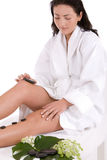 Pretty brunette giving herself a hot stone massage Royalty Free Stock Images