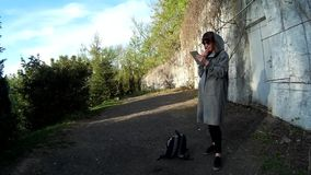 Pretty brunette using digital tablet at the park 2. Pretty brunette in a gray cardigan using digital tablet at the park in front of the concrete wall with dry stock footage