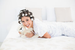 Pretty brunette in hair rollers cuddling her teddy on bed Royalty Free Stock Photos