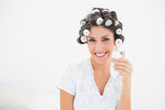 Pretty brunette in hair rollers holding glass of water smiling a Stock Photos