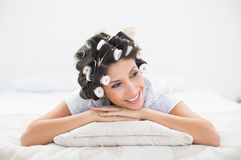 Pretty brunette in hair rollers lying on her bed Stock Image
