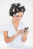 Pretty brunette in hair rollers using smartphone on bed Stock Photography