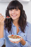 Pretty brunette having bowl of cereal and fruit Royalty Free Stock Photos