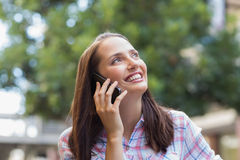 Pretty brunette having a phone call and looking away Royalty Free Stock Image