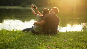 Pretty brunette with her boyfriend taking selfie by her smartphone while sitting near the lake in the city park during stock video footage