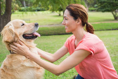 Pretty brunette with her dog in the park Stock Photo
