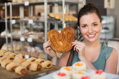 Pretty brunette holding heart shape pastry Stock Photos