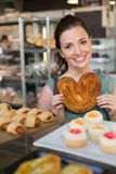 Pretty brunette holding heart shape pastry Royalty Free Stock Image